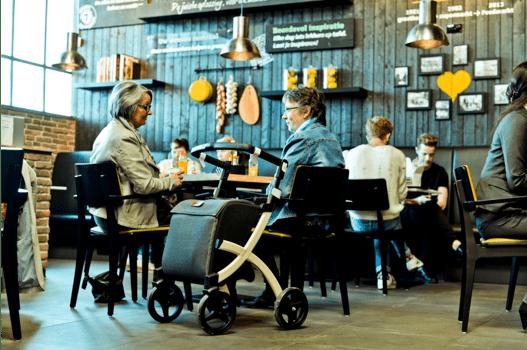 Junto a mi Rollz Flex acompañada de una amiga en una mesa de una cafetería tradicional decorada de madera oscura conversando y tomando un café, después de la compra